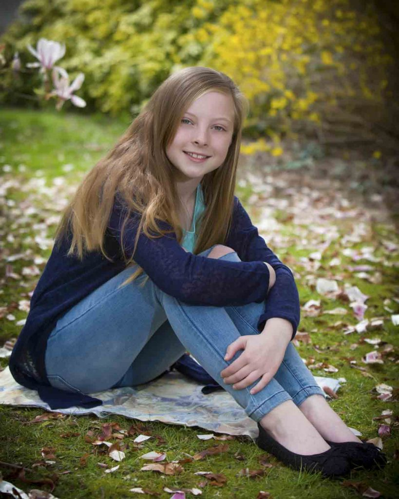 girl outside sitting near blossoms