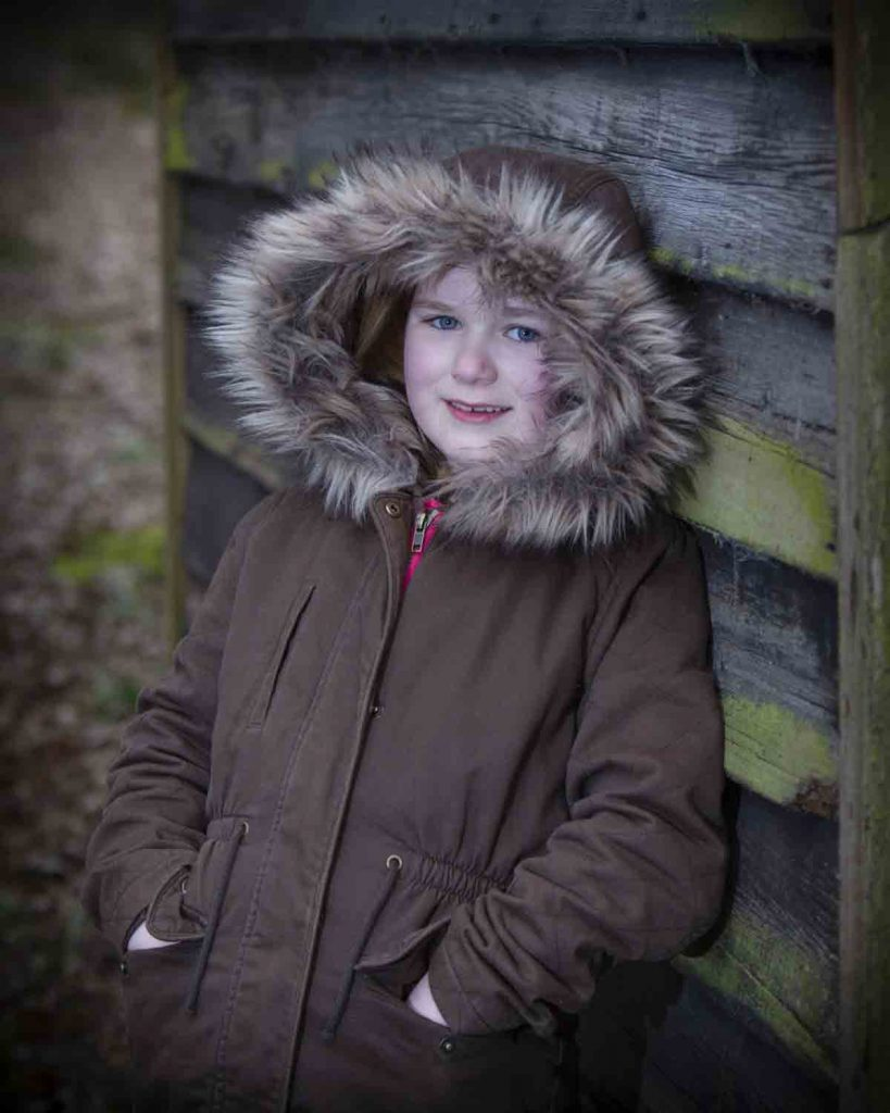 girl leaning against shed wearing hoodie