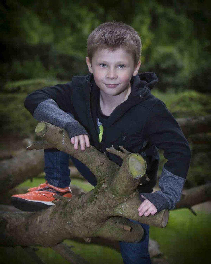 boy kneeling on a tree