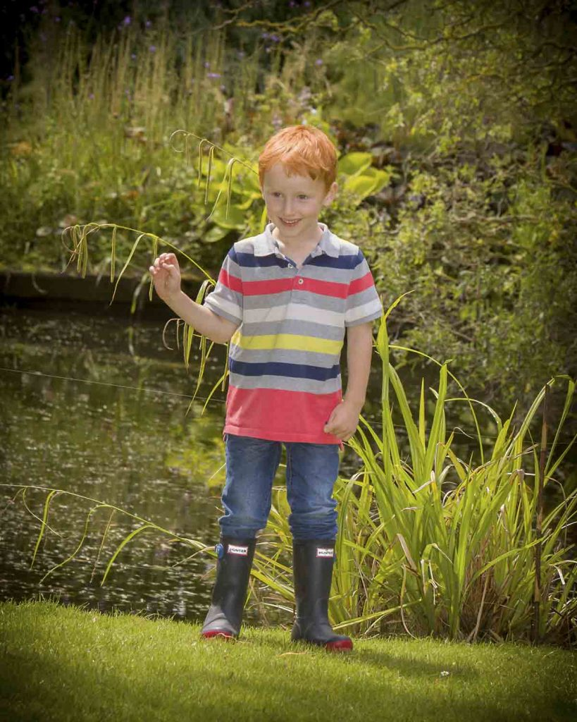 boy in wellington boots by pond