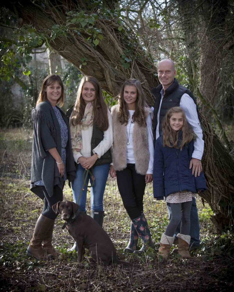 family outside with dog under a tree