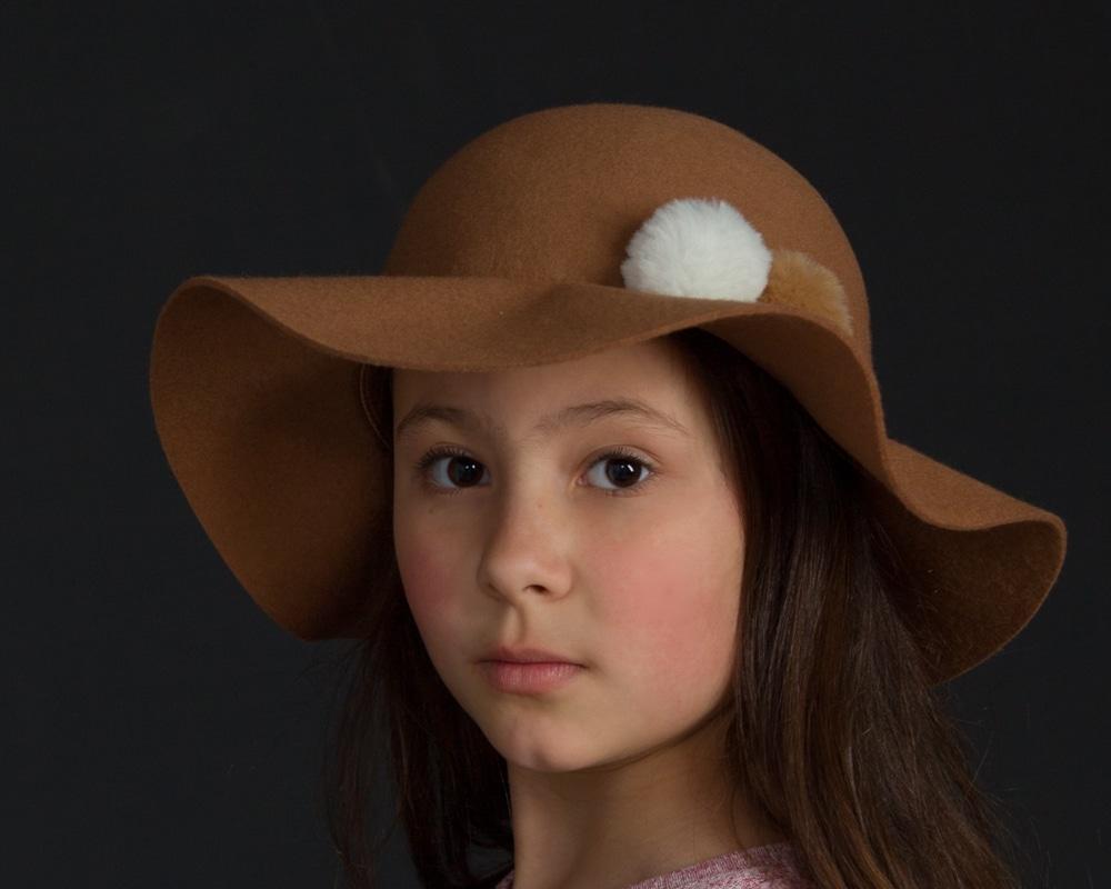 portfolio - girl in studio against a dark background with a hat on